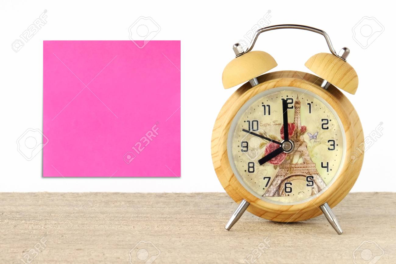 blank note paper and vintage wooden alarm clock on table background