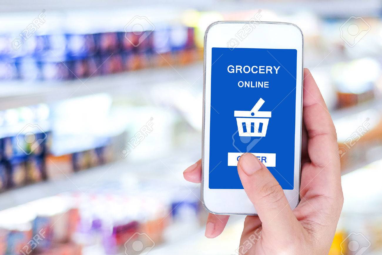 Hand holding smart phone with grocery shopping online on screen over blur supermarket background, retail business and technology concept - 52477707