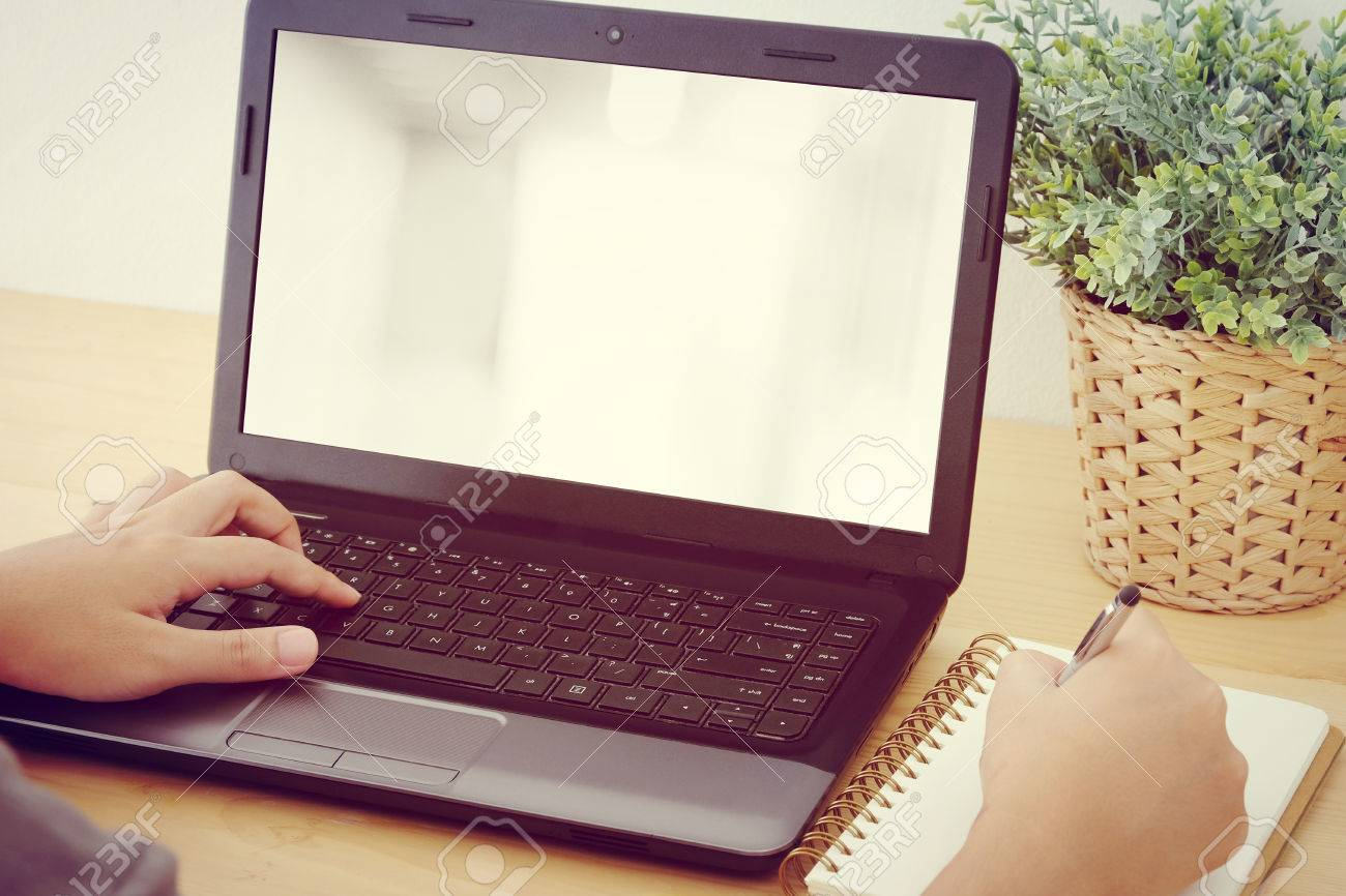hand typing laptop and writing on notebook background for mock