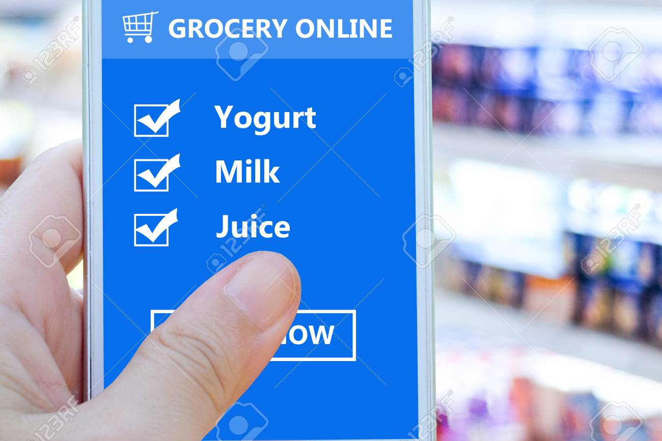 hand holding smart phone with grocery shopping check list online on screen device over blur product
