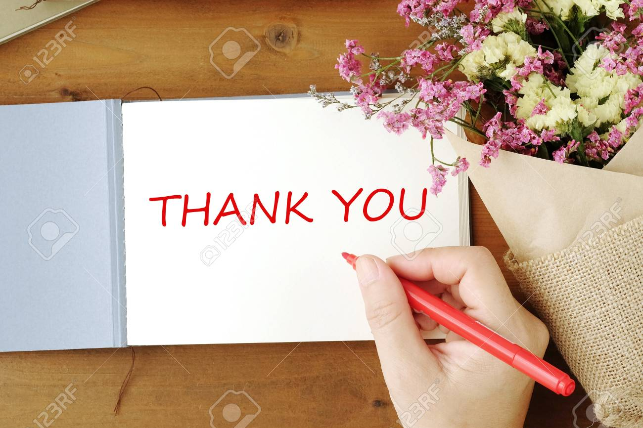 Hand holding red pen over thank you card and flower bouquet on hand holding red pen over thank you card and flower bouquet on wood table background stock izmirmasajfo