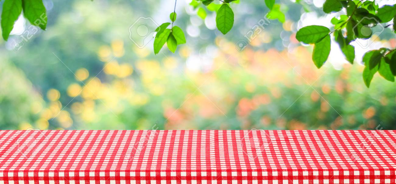 empty table with red tablecloth over blur green tree and bokeh