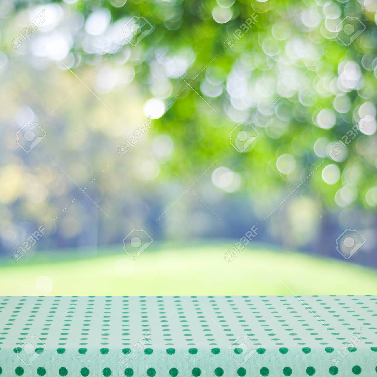 Empty Table With Green Tablecloth Over Blur Garden And Bokeh