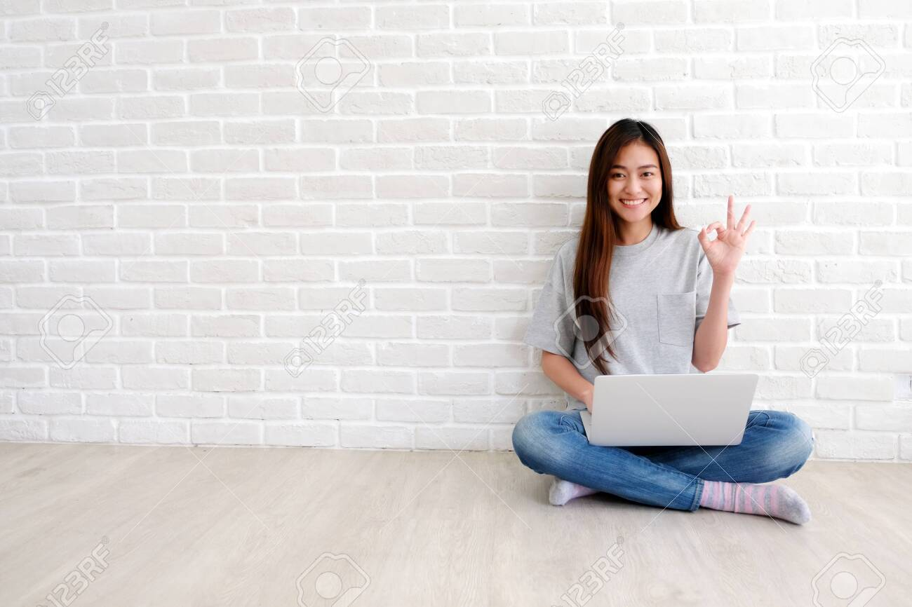 Young asian woman showing ok hand sign and smiling while working with laptop computer in white room with copy spce, people with positive gesture - 123741315
