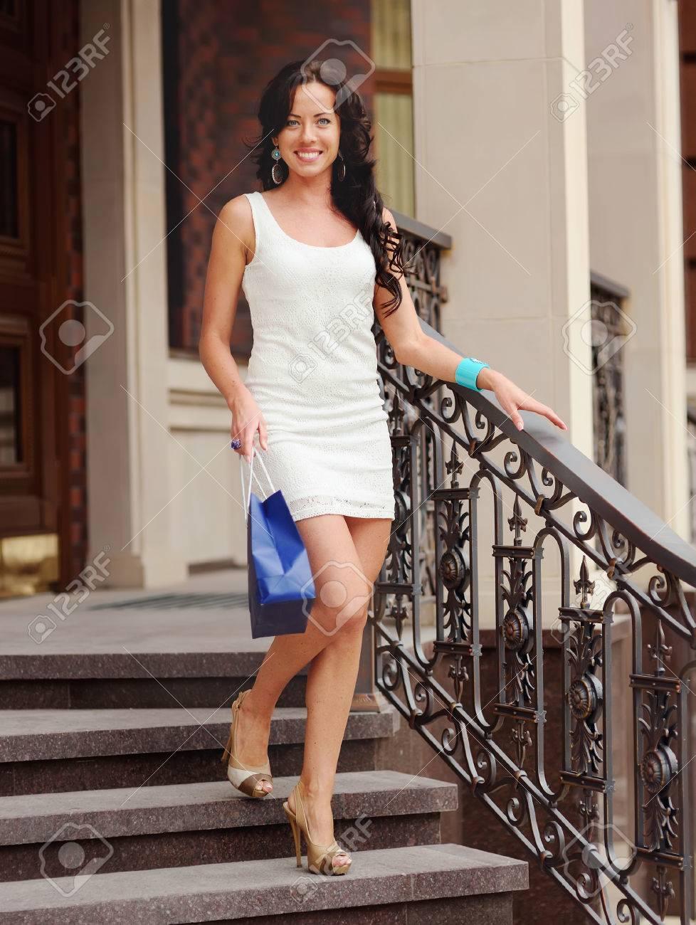 Beautiful Woman In White Dress With Shopping Bag Walking Down ...