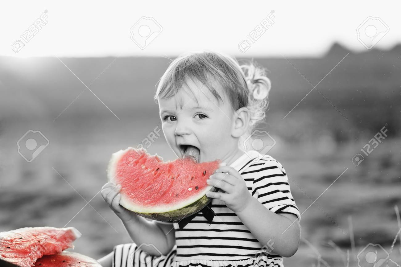Black and white with color accent cute girl kid sitting wih big watermelon at countryside having fun black and white
