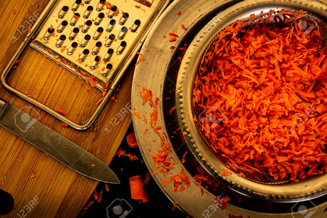 View of grated carrots in a bowl along with the grater and knife - 164966824