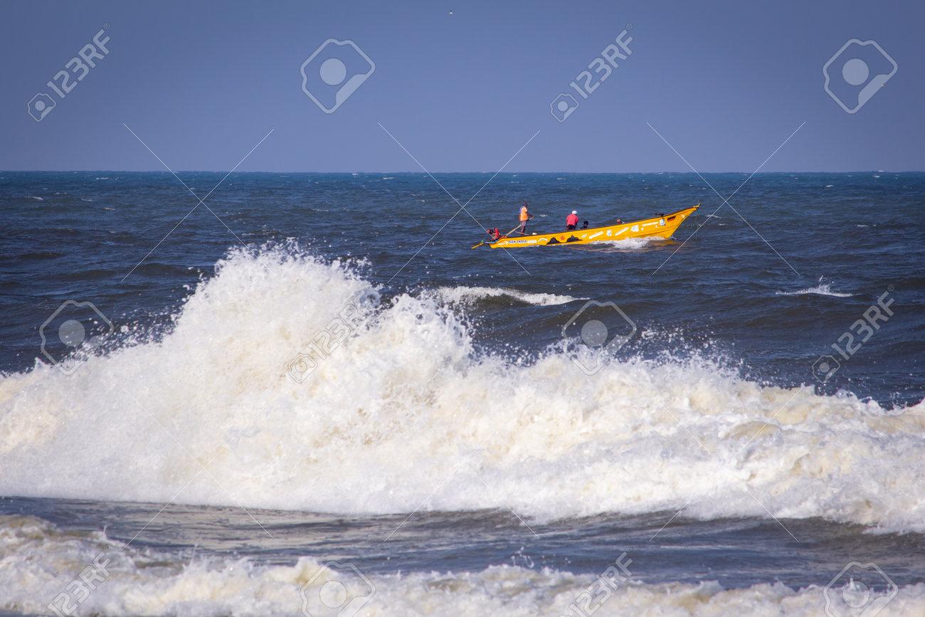 Kovalam, Tamil Nadu, India - February 04 2021: Beautiful view of the waves and the fishing boat along the Kovalam beach, Chennai, India. Fishermen venturing into sea. - 164924693