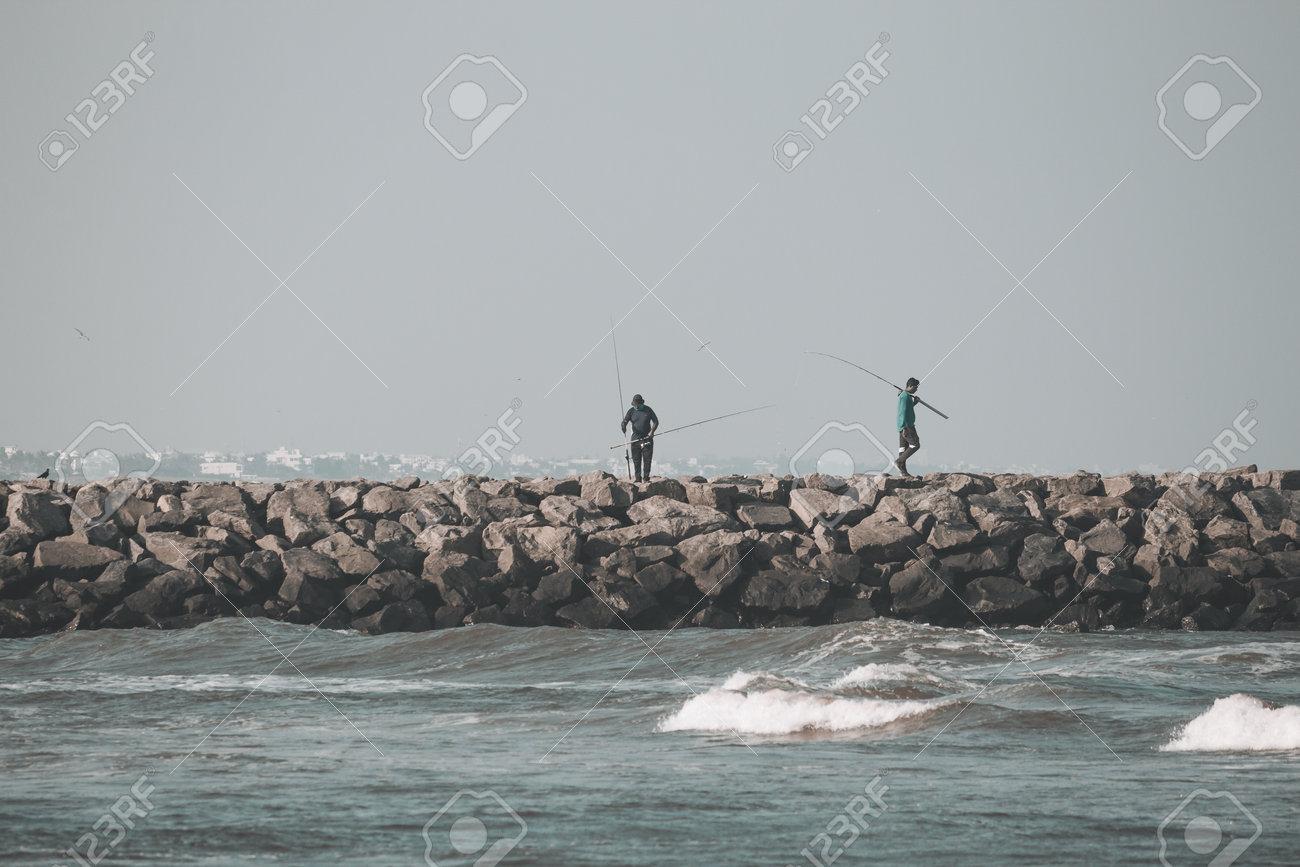 Kovalam, Tamil Nadu, India - February 04 2021: People fishing over the rocks along the Kovalam beach, Chennai, India. - 164925834