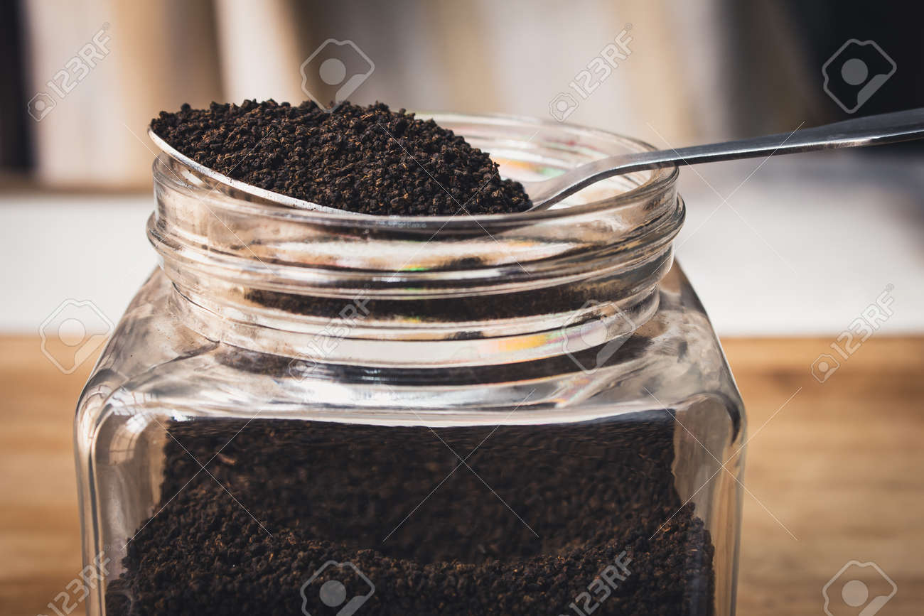 View of finest tea powder in a spoon placed over a glass container. Common dust tea used in India - 165099543