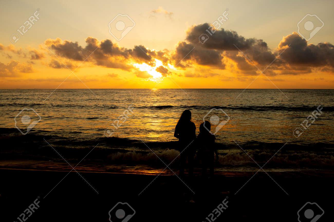 Kids in silhouette watching the sunrise in Marina Beach, Chennai, India - 166095401