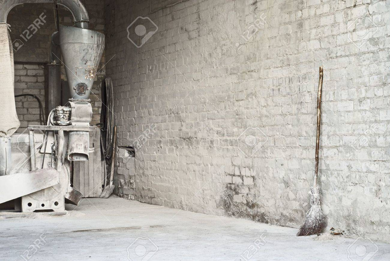 electric corn mill and wooden broom at the wall Stock Photo - 16719536