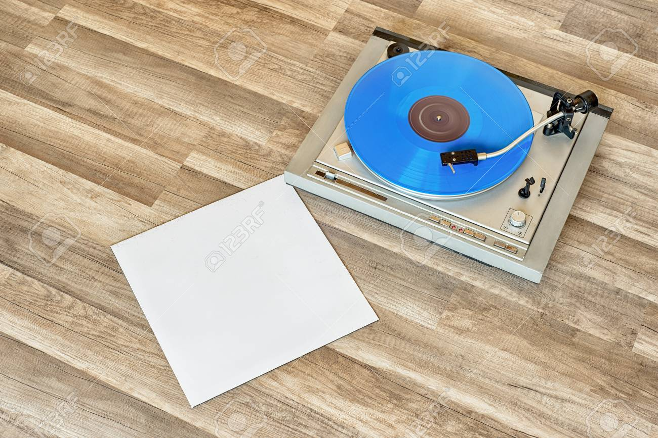 Blue Vinyl Record Spining On The Turntable Grunge Wooden Floor