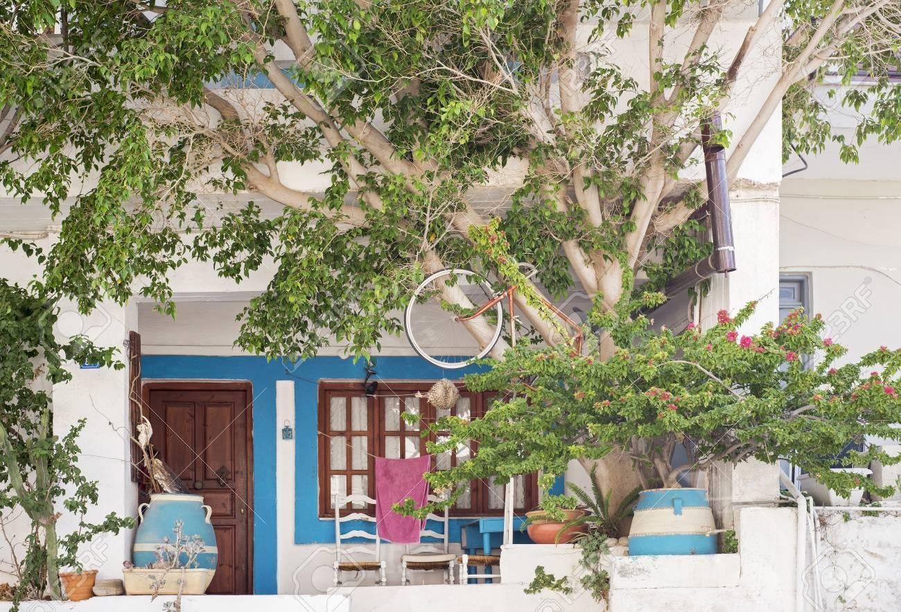 Huis gevel met bloempotten stoelen en boom zomer in elounda