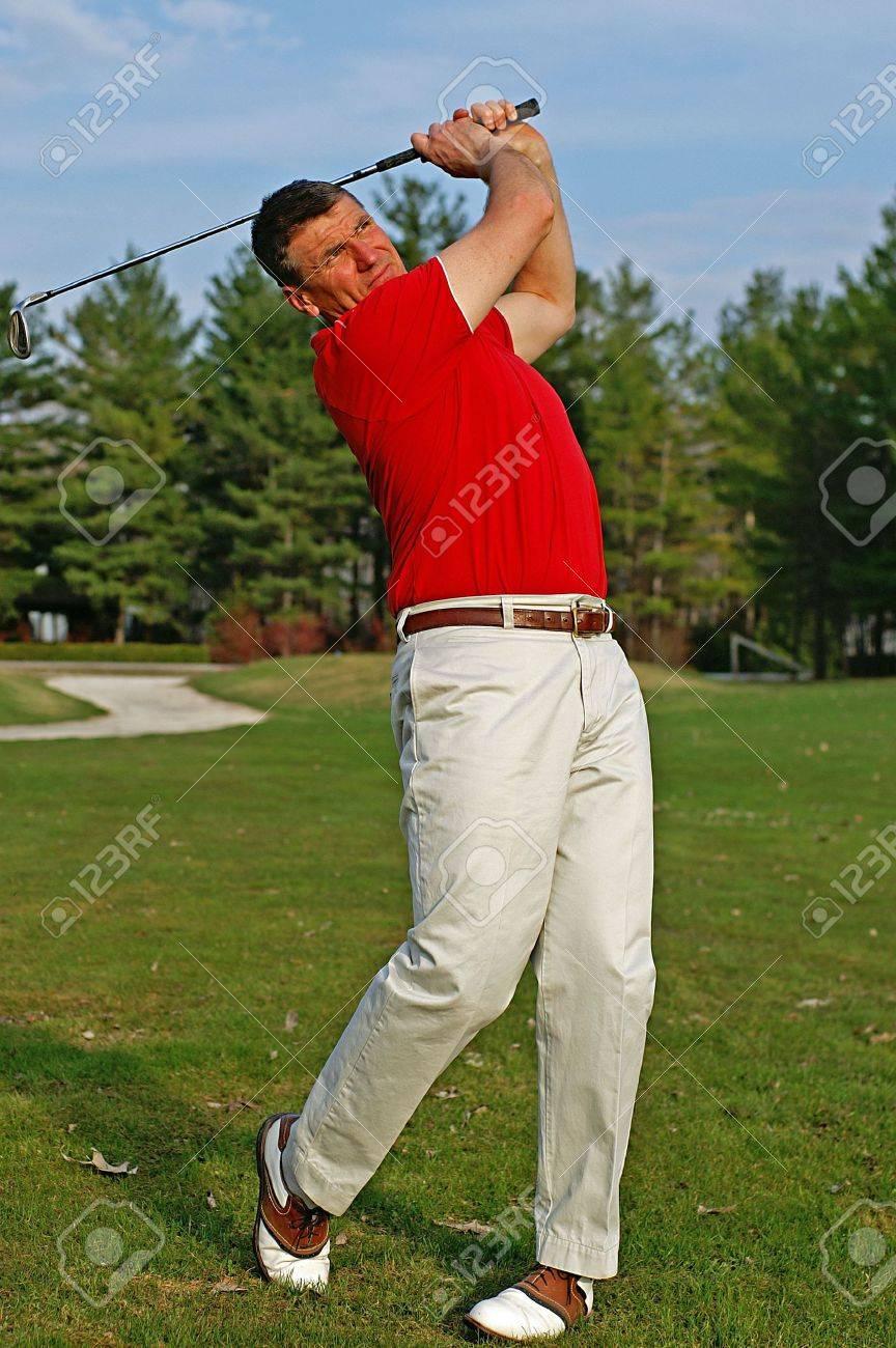 Early season golfer follows the flight of his ball down the fairway. - 2904043