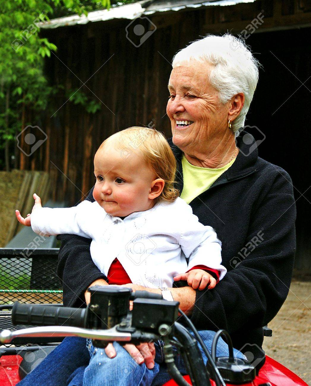 A toddler sits with her grandmother in front of a barn - 3223191