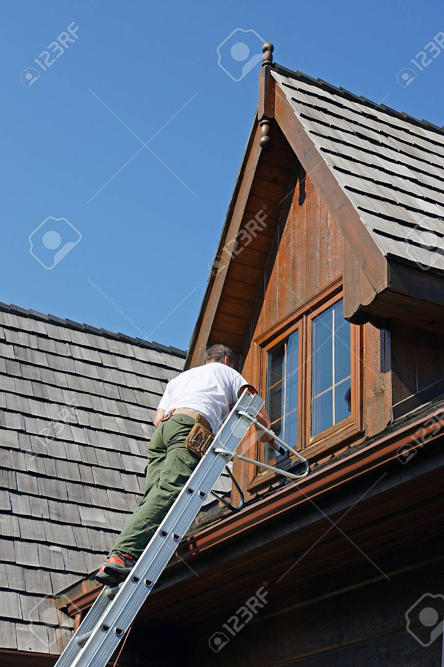 Painter on a ladder staining woodwork on a log home - 3616132