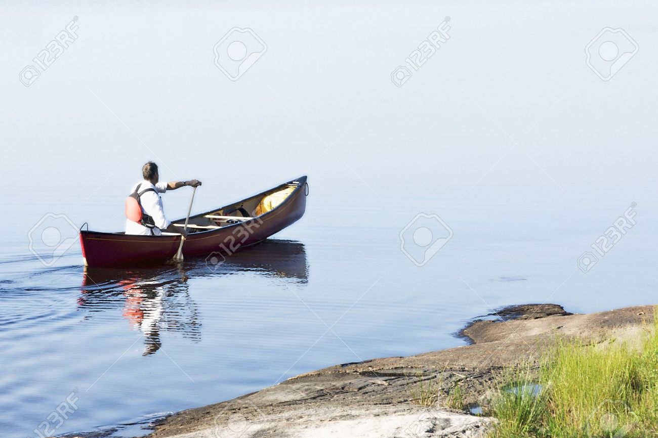 A man out for a morning paddle in a red canoe - 7580799