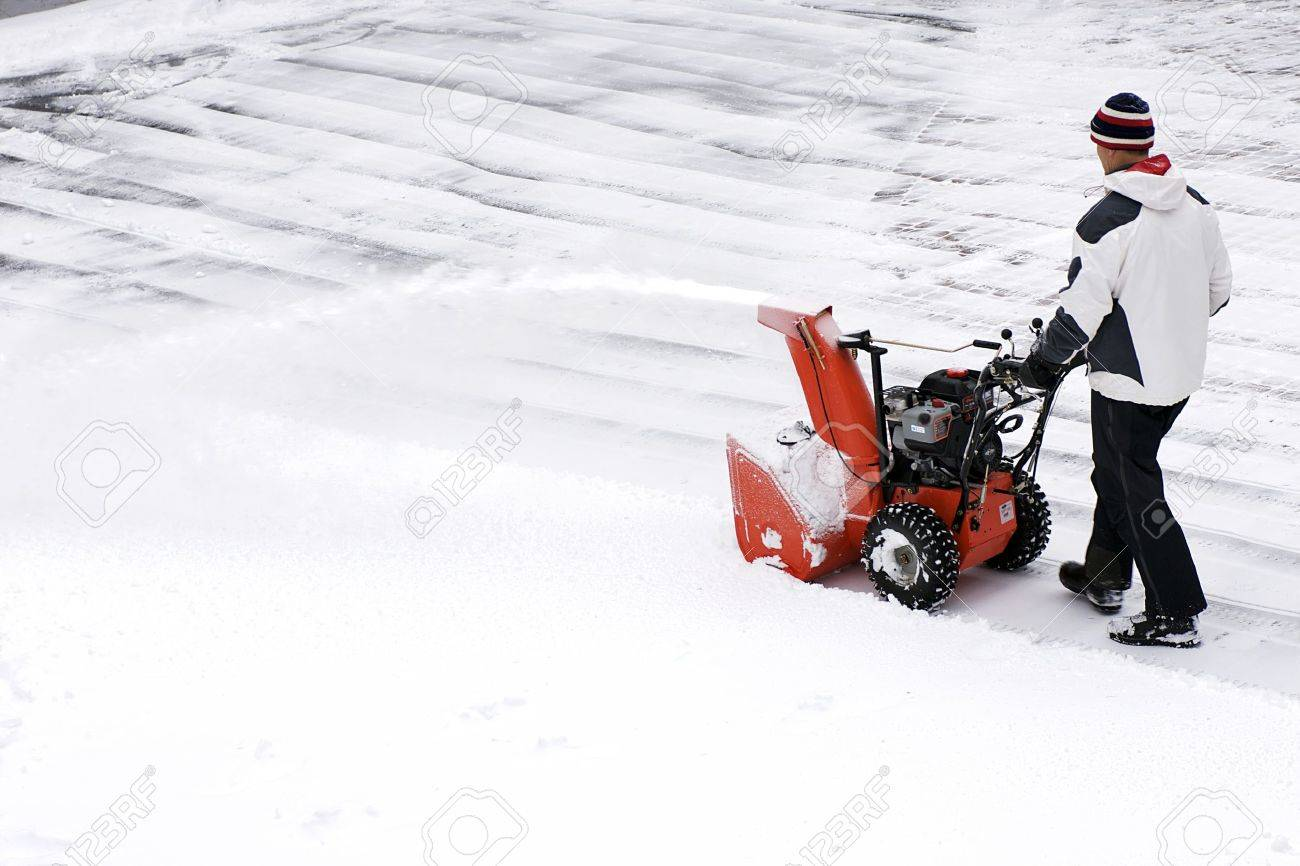 A man clears snow from a driveway with a snow thrower after a winter storm in Canada. - 11945045