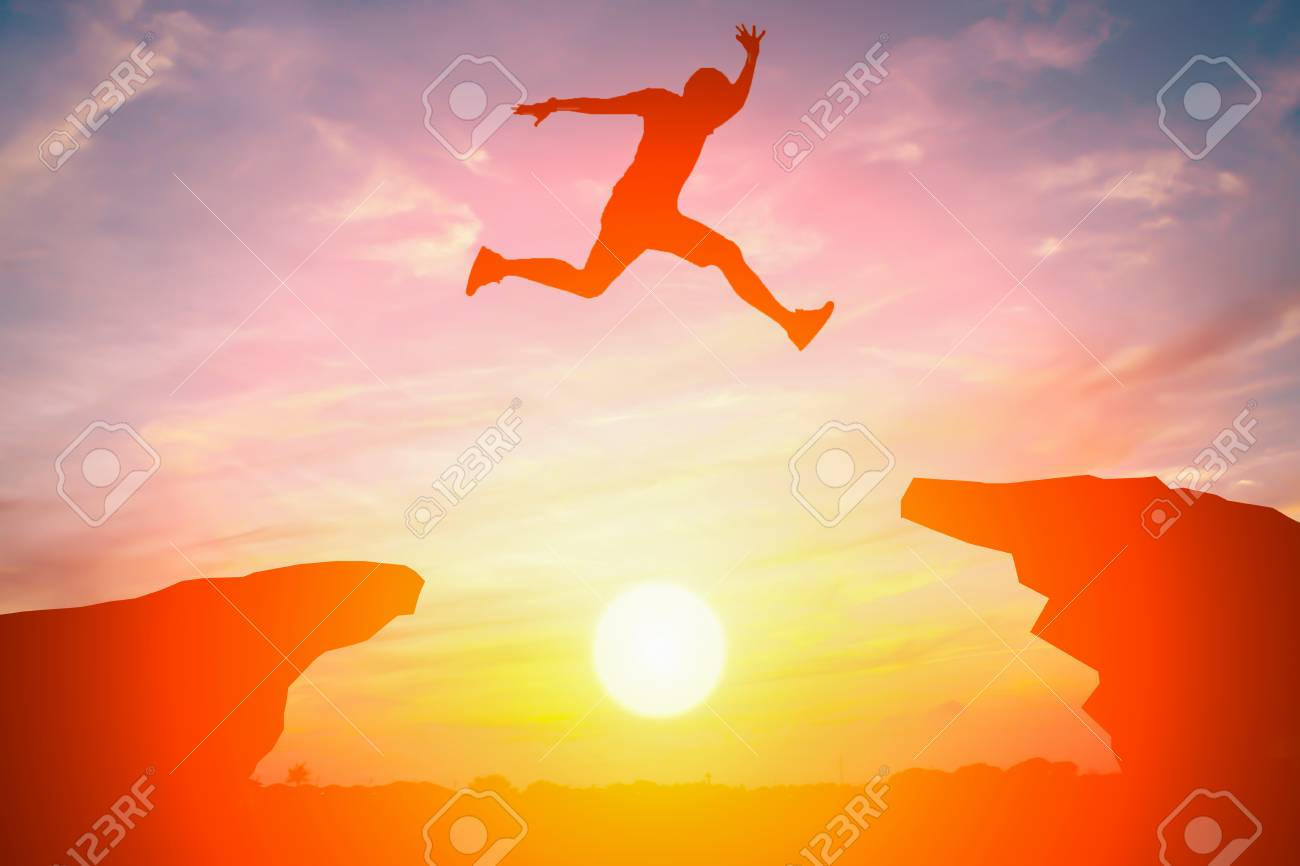 Silhouette of man jump over the cliff obstacle in sunset - 82807710