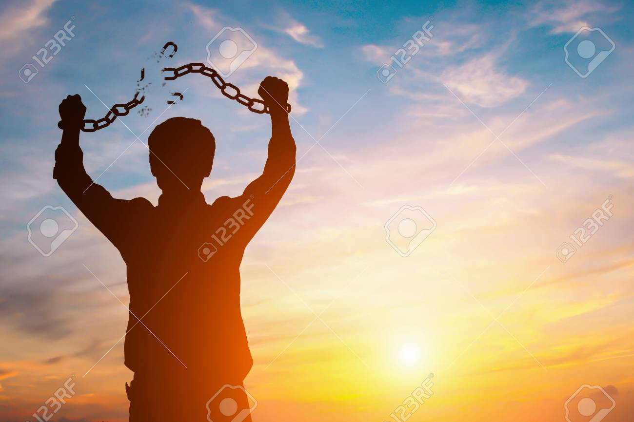 Silhouette image of a businessman with broken chains in sunset - 87173260