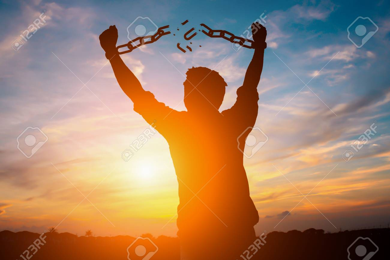 Silhouette image of a businessman with broken chains in sunset - 87173291