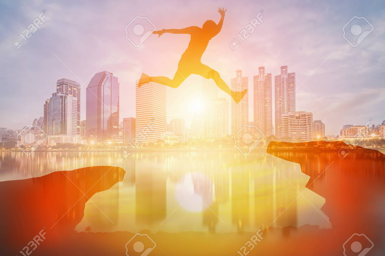Double exposure of a man jump over the cliff obstacle in sunset and city - 90573087