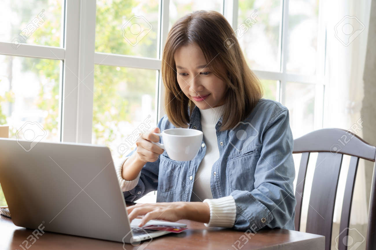 Happy Asian woman shopping online and paying by credit card in coffee shop. technology and ecommerce concept - 170974801