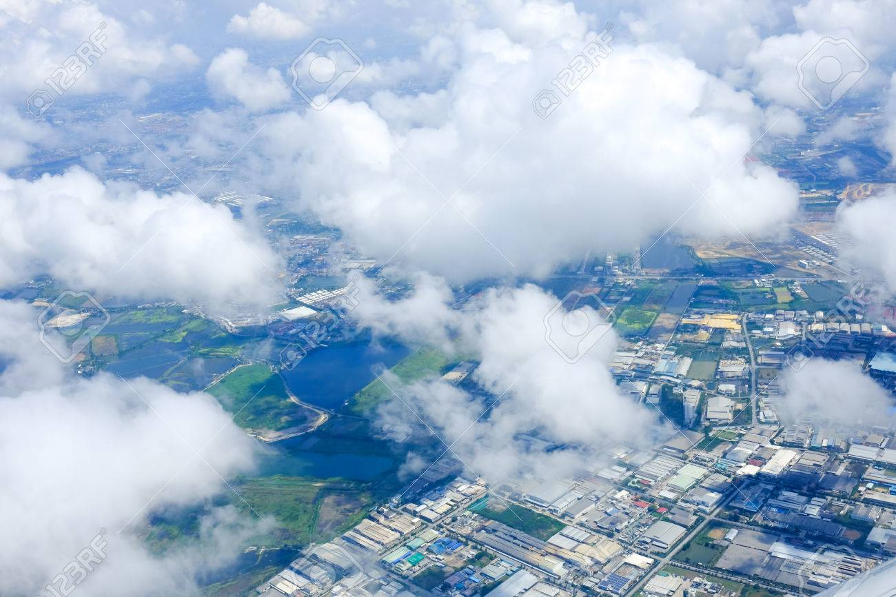 Looking Throung Airplane Window Above The Clouds And The City