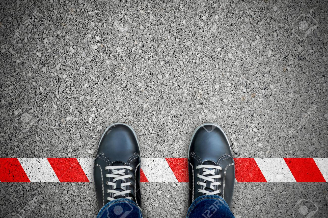 Black shoes standing on the red-white line. Breaking the rule. It's prohibited and not allowed. It's limited. It's the end. - 101860438