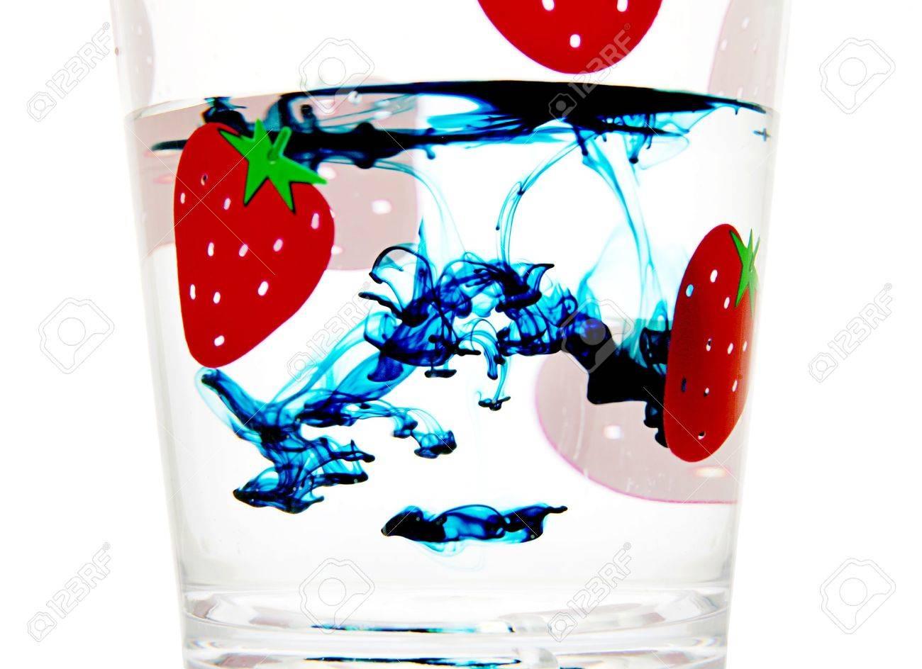 aqua food coloring drops in clear liquid inside a glass
