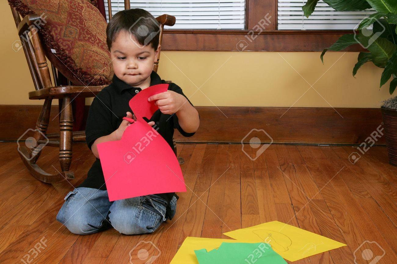 Fußboden Aus Papier ~ Eine junge männliche kind schneiden papier streifen auf dem fußboden