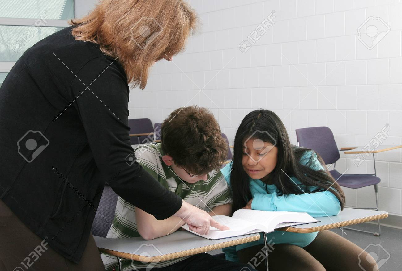 one woman teacher helping two young students in class Stock Photo - 4363382