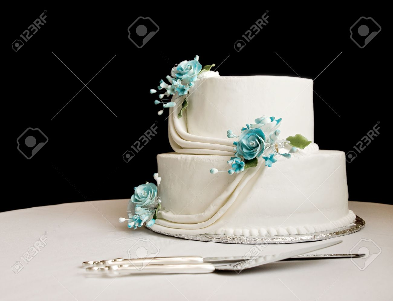 White wedding cake with blue flowers on a table with a black stock stock photo white wedding cake with blue flowers on a table with a black background izmirmasajfo Images