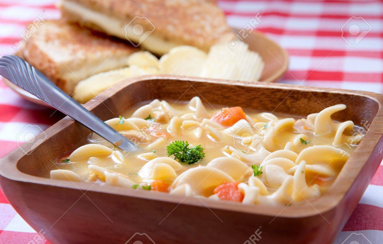 One Bowl Of Chicken Noodle Soup And A Grilled Cheese Sandwich Background On Classic Red And