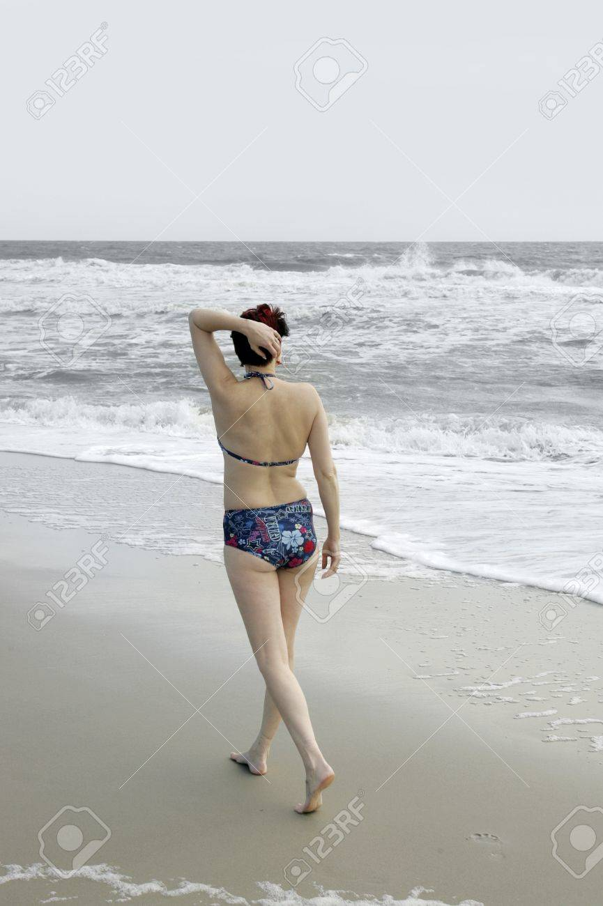 one young adult fit woman walking in a bikini on the beach Stock Photo - 7875227