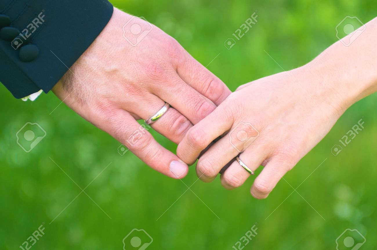 Bride And Groom Hands With Wedding Rings On Their Finger Holding ...