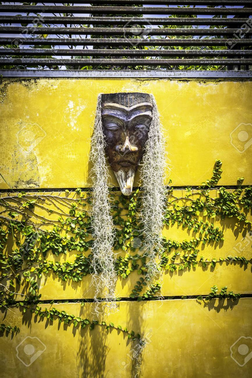 Plant With Wooden Carving Mask Decoration On Yellow Wall Stock Photo ...