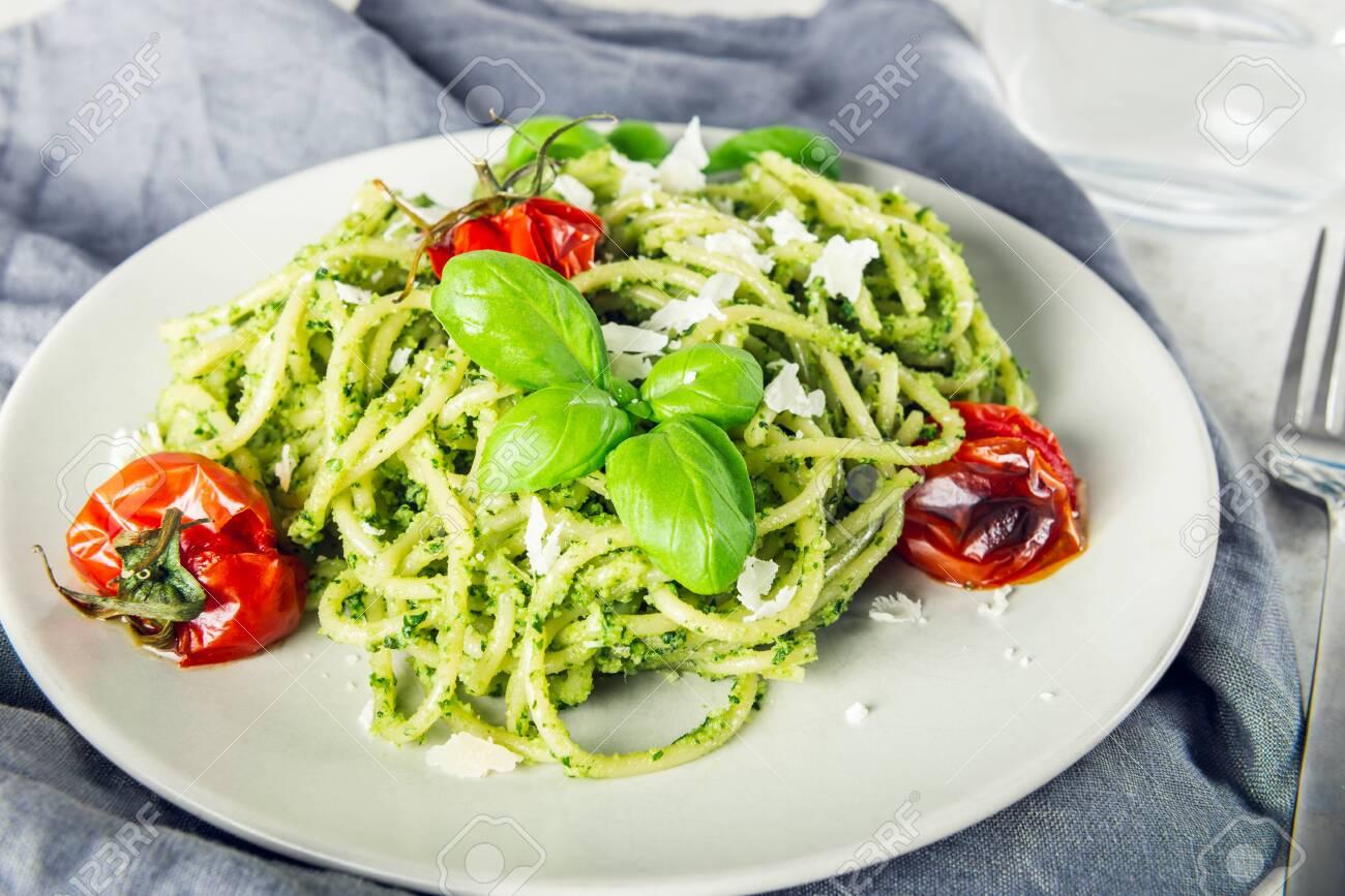 Pasta spaghetti with homemade pesto sauce, roasted tomatoes and fresh basil leaves, vegetarian food - 144520896