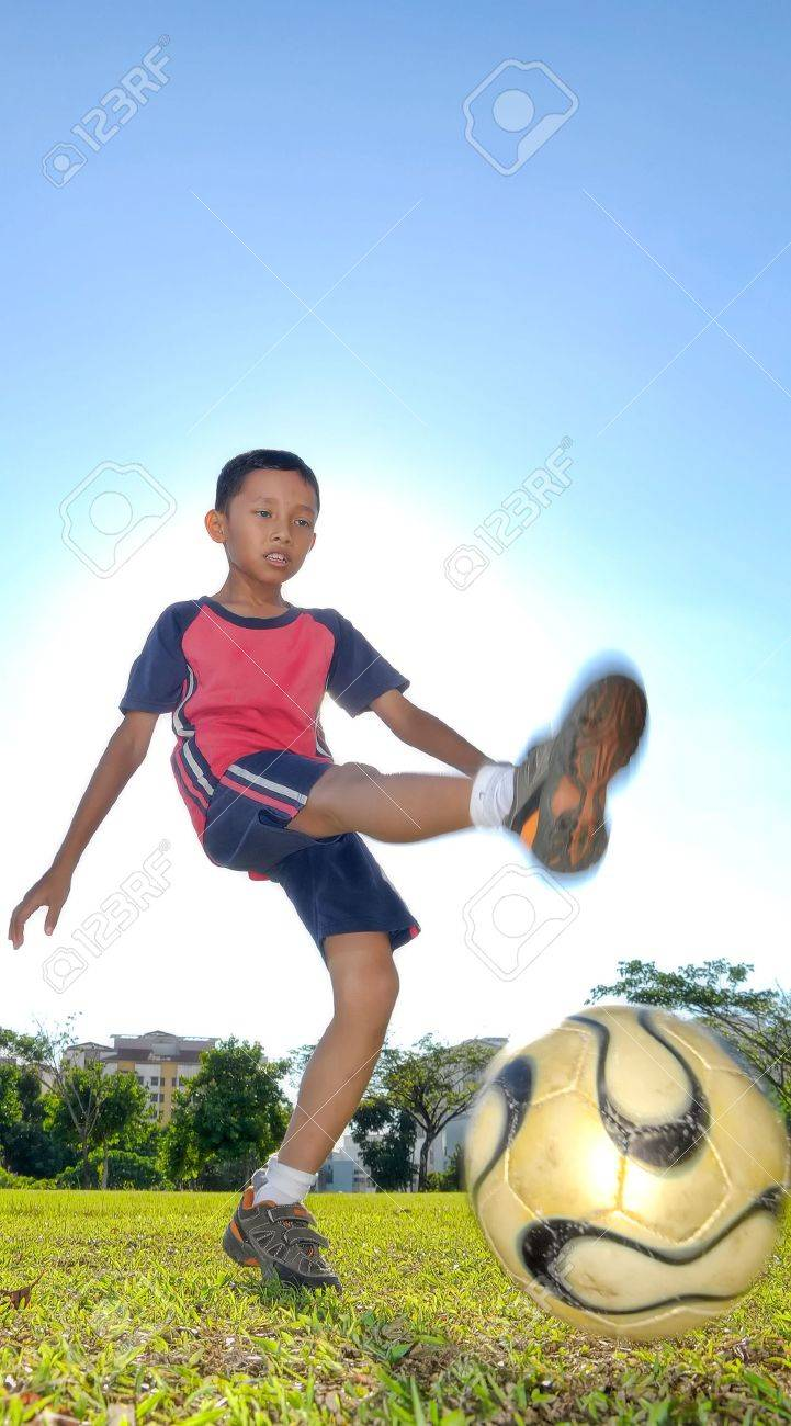 A boy is kicking a ball during evening Stock Photo - 4808259