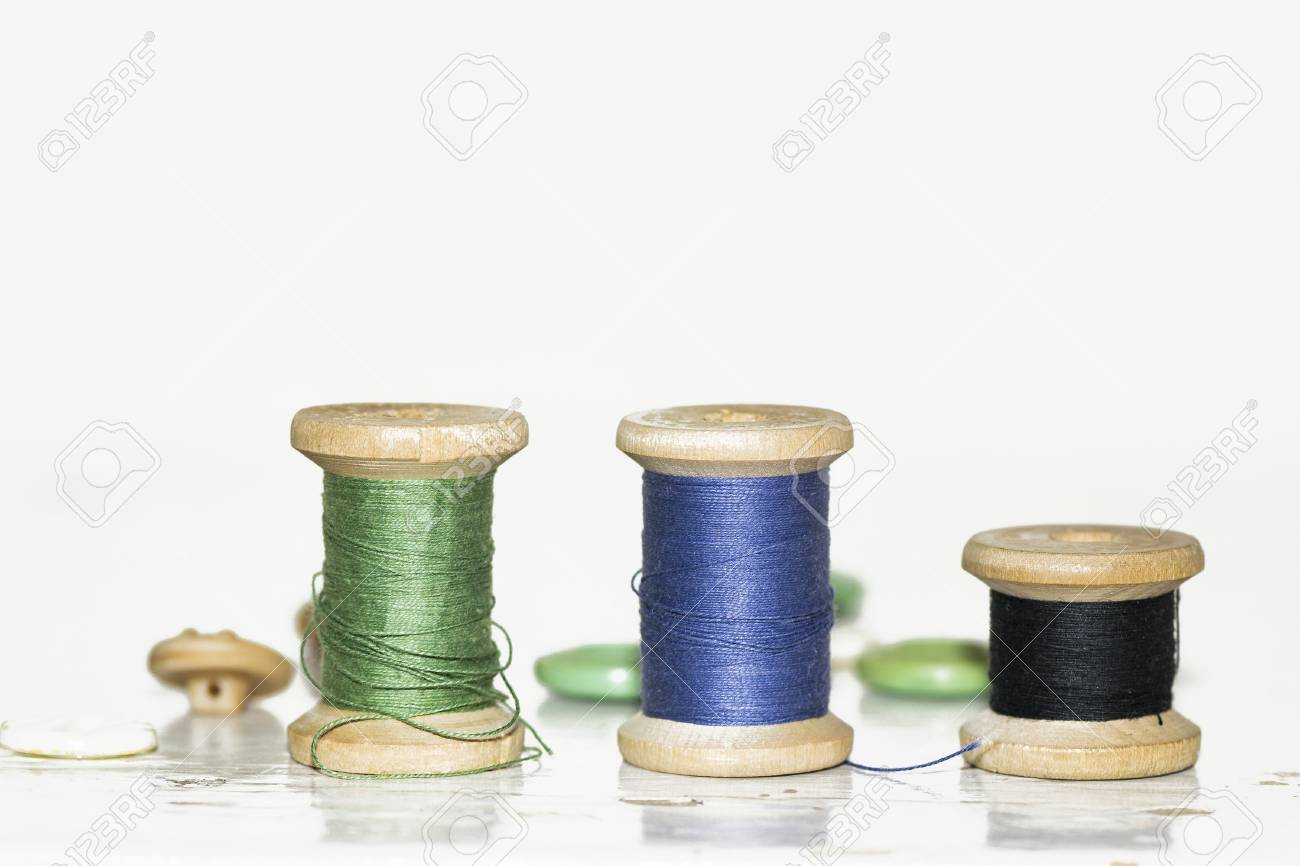 Old Wooden Spools Of Blue Green And Black On An Old Painted