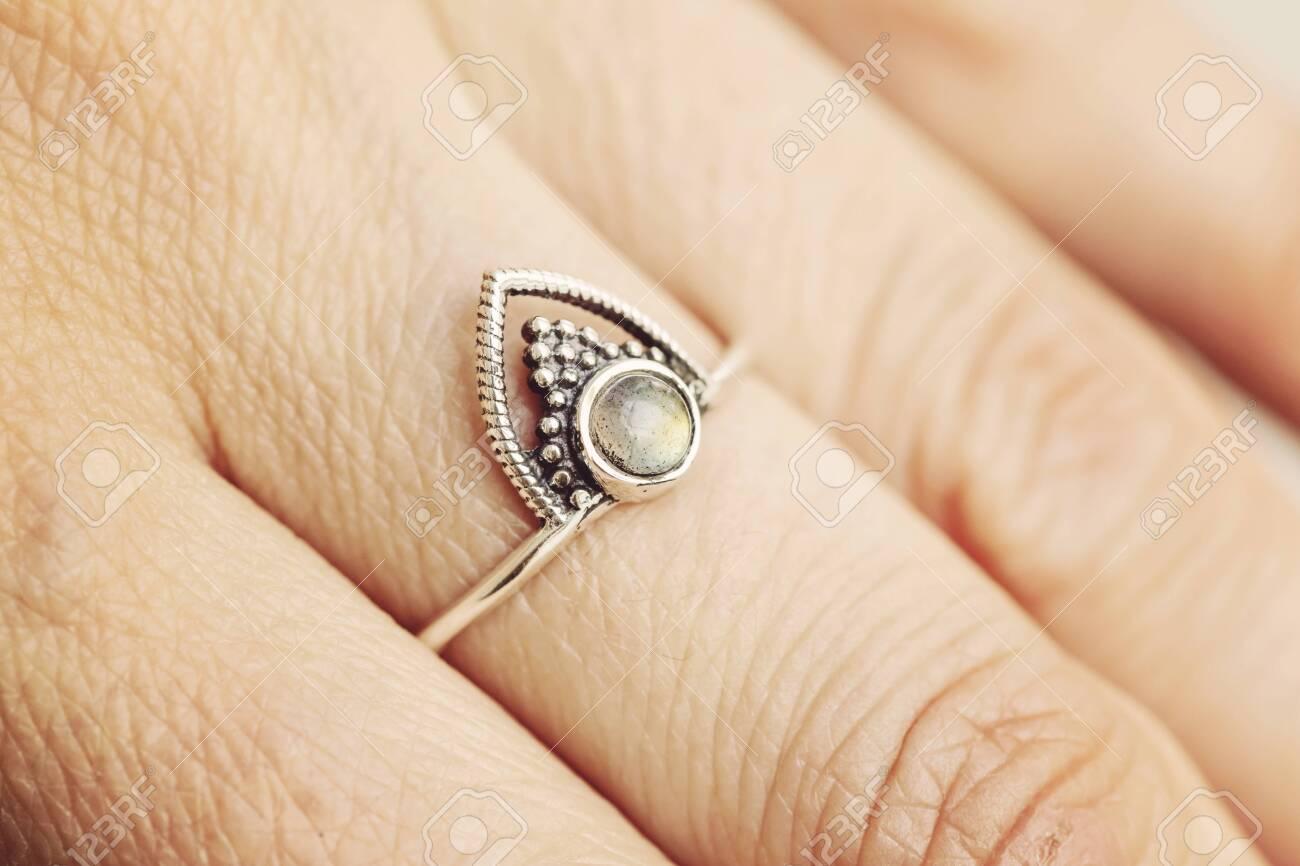 Female hand wearing silver ring with labradorite gemstone - 122350228