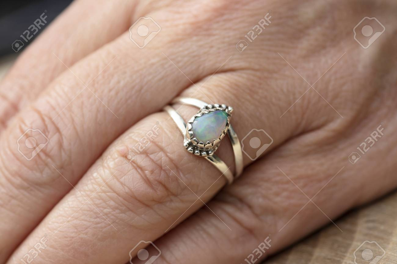 Silver ring with opal gemstone caboshon on female hand - 123494658