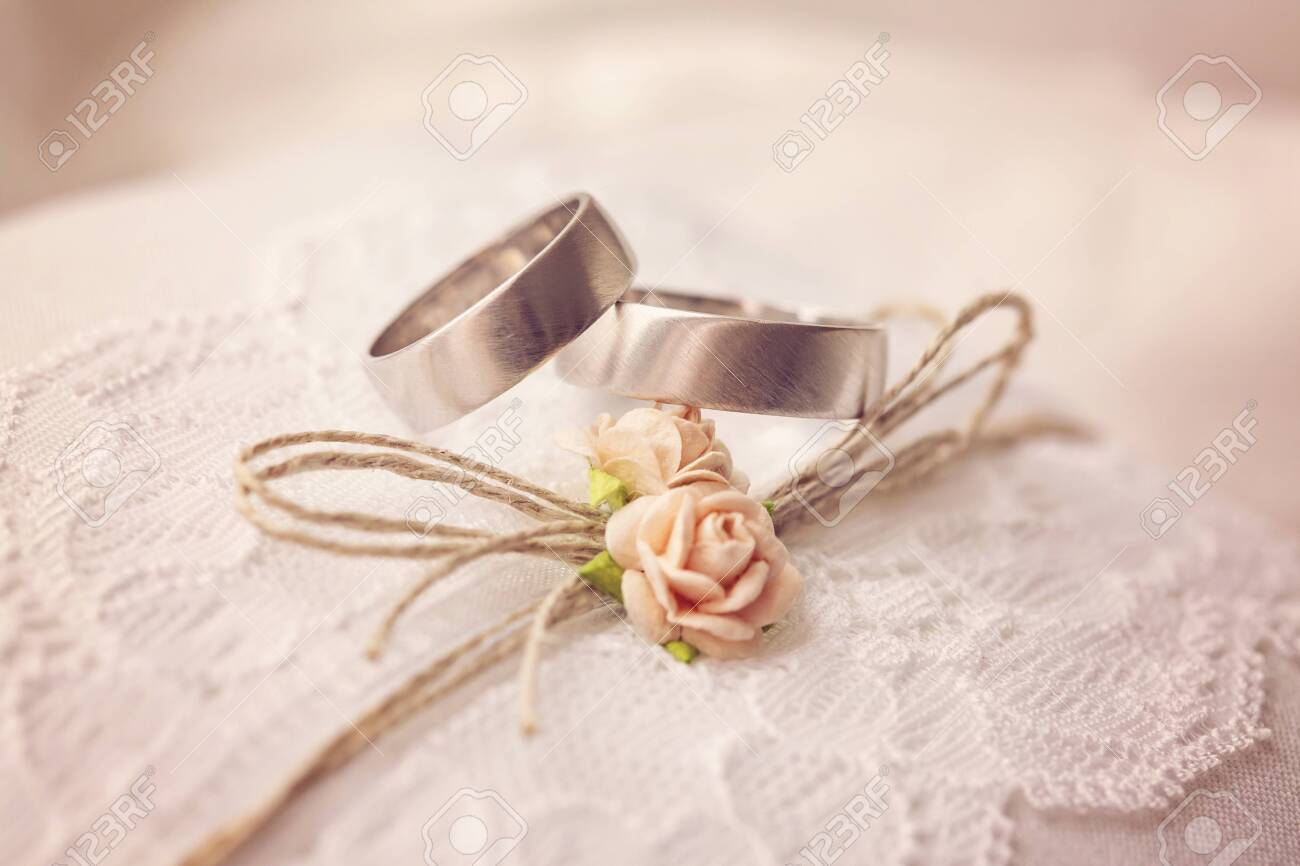 Wedding ring on lace pillow with sweet artificial small rose blossoms - 129082776