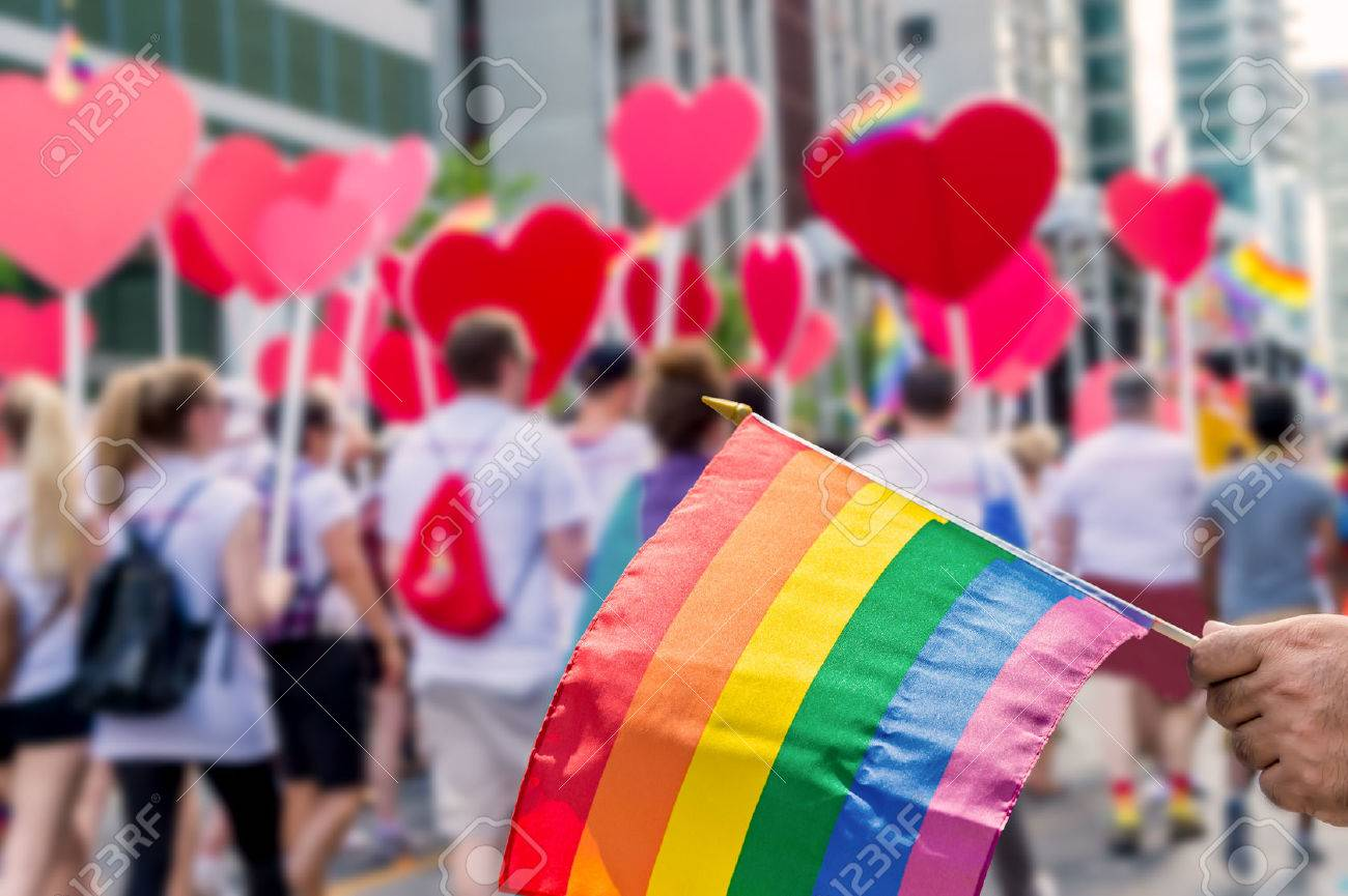 Rainbow flag floating in front of blurred pride participants holding hearts - 61140553