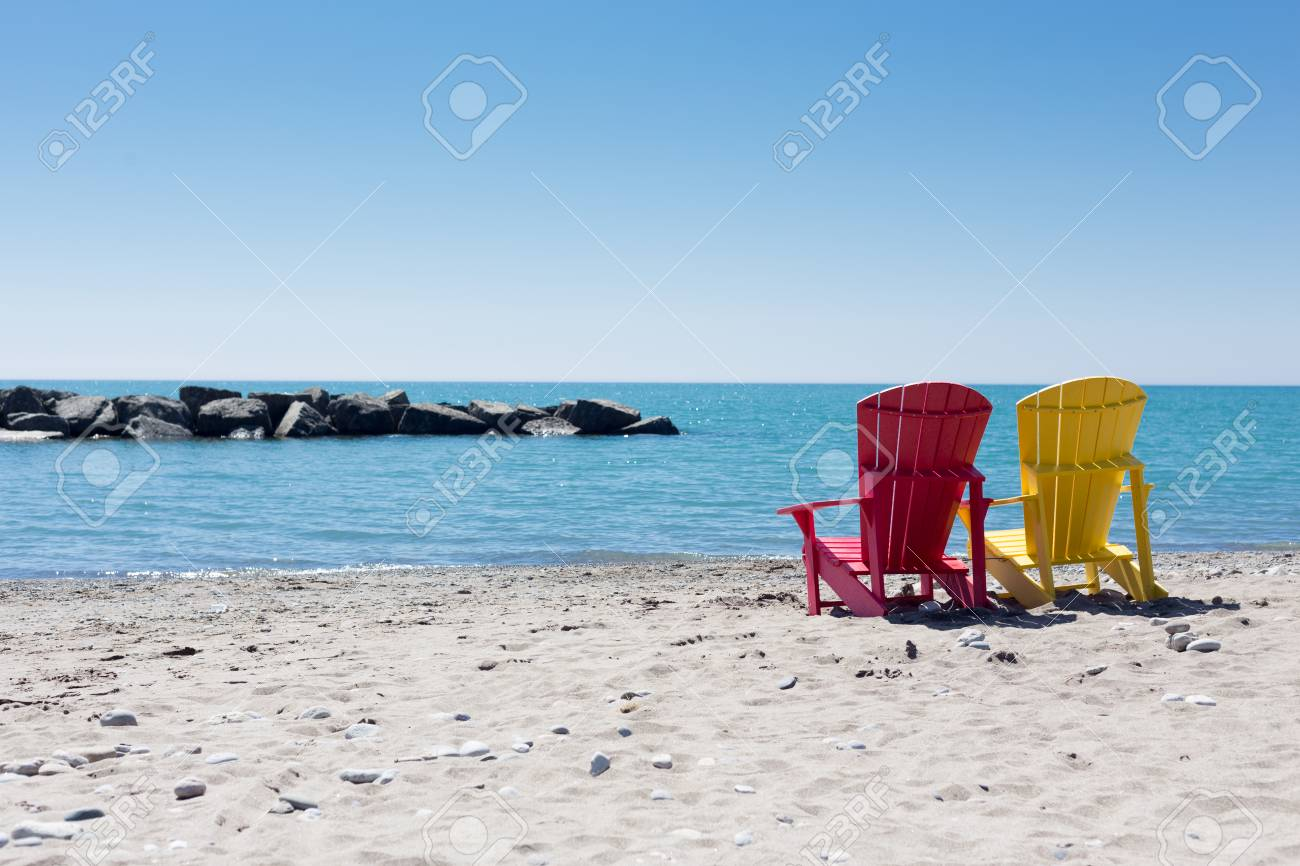 Beach Scene With Two Adirondack Chairs In Yellow And Pink Color At Lake  Ontario Toronto Stock