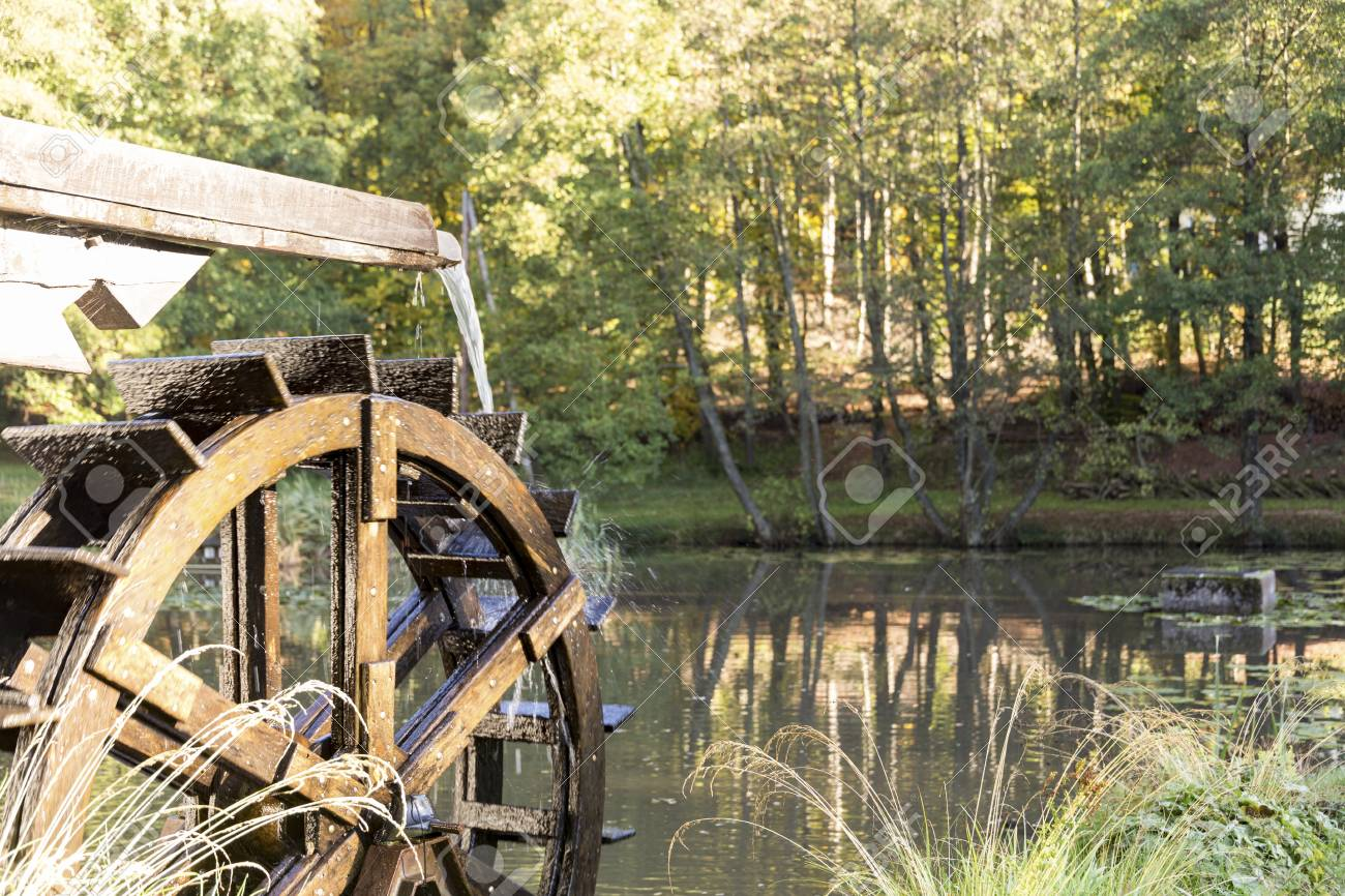 old vintage wooden wheel water mill moving water splashes drop
