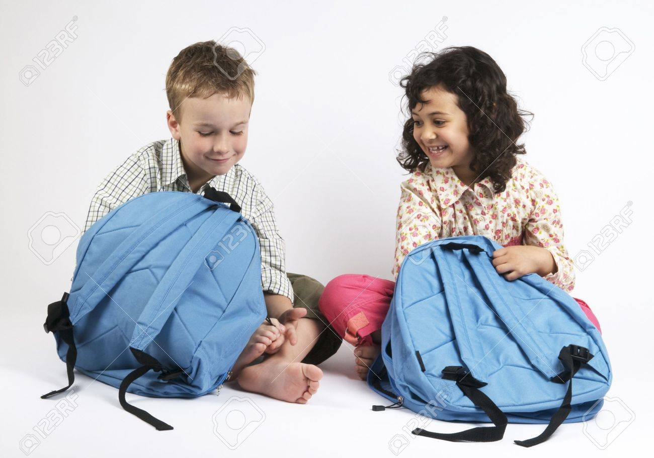 Two Kids Going On A Vacation Packing Their Backpacks Or Use Stock