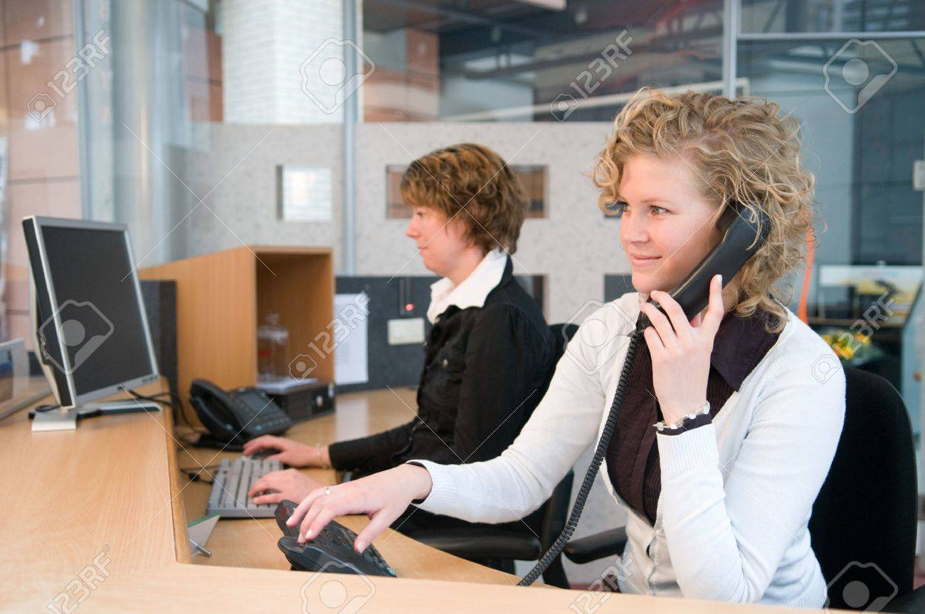 two professional women working at a front desk stock photo stock photo two professional women working at a front desk