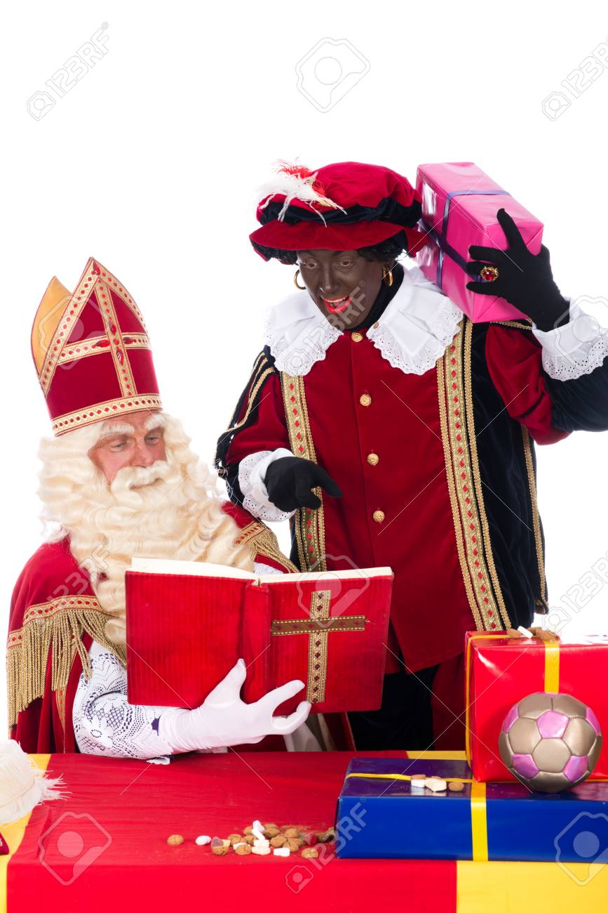 bee7b687d8c27 Sinterklaas is reading in his book while Zwarte Piet is with him Stock  Photo - 23421959